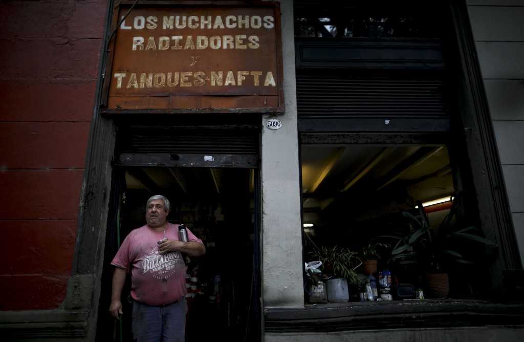 "In this March 17, 2020 photo, Gustavo Lachaga holds his ""mate"" drink outside his radiator repair shop in Buenos Aires, Argentina. Since the outbreak o..."
