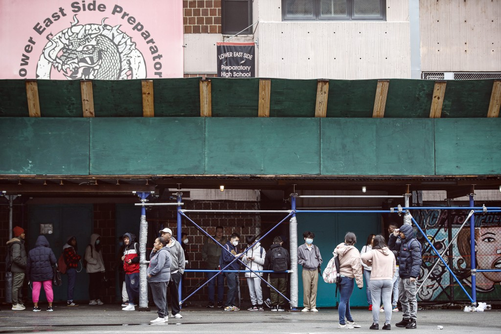 Students wait on premises to receive school laptops for home study at the Lower East Side Preparatory School, Thursday, March 19, 2020, in New York, a...