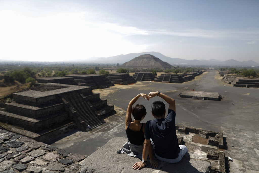 South Korean tourists Myung Hee Lee, left, and Byung Ho Im, form a heart with their hands as they pose for pictures atop the Pyramid of the Moon, in T...