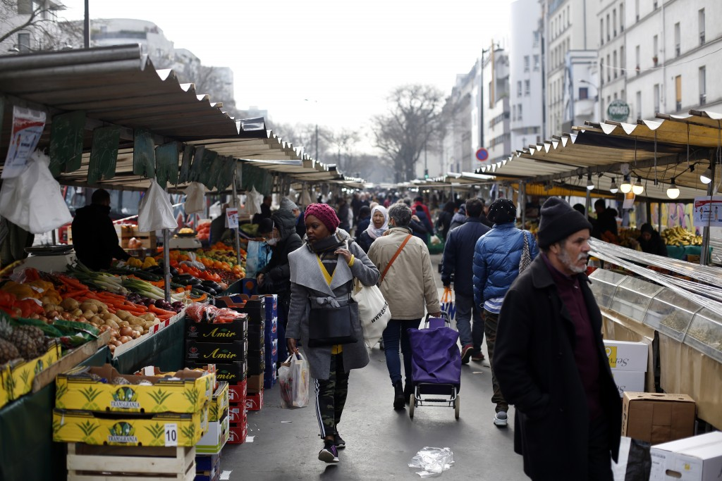 People walk in the open air market of Belleville, in Paris, Friday, March 20, 2020. French President Emmanuel Macron said that for 15 days starting at...