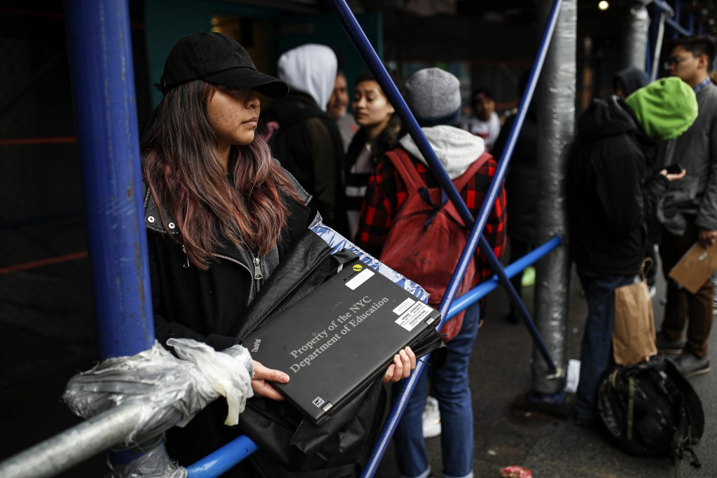 Anna Louisa, 18, receives her school laptop for home study at the Lower East Side Preparatory School, Thursday, March 19, 2020, in New York, as corona...