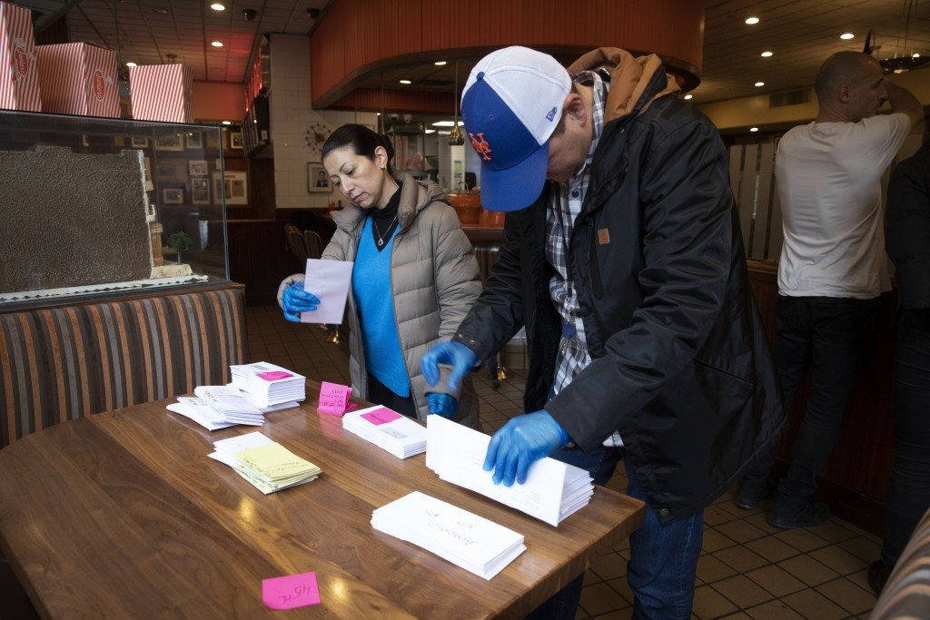 Employees of Junior's Restaurant sort paychecks for fellow workers who are picking them up, Thursday, March 19, 2020 in the Brooklyn borough of New Yo...