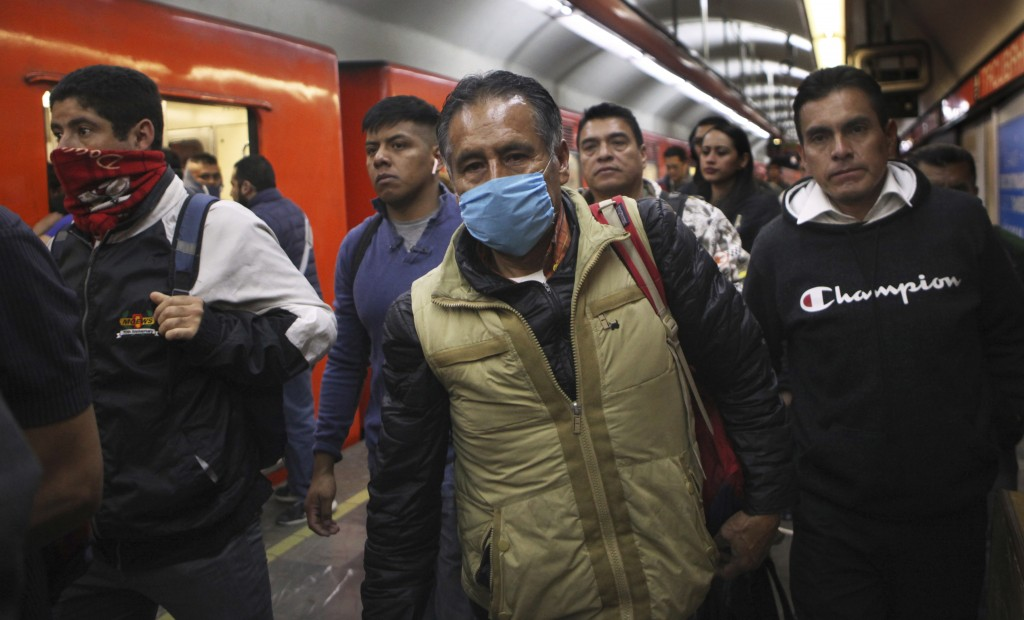 A commuter wears a protective mask as a precaution against the spread of the new coronavirus in the metro in Mexico City, Thursday, March 19, 2020.  (...
