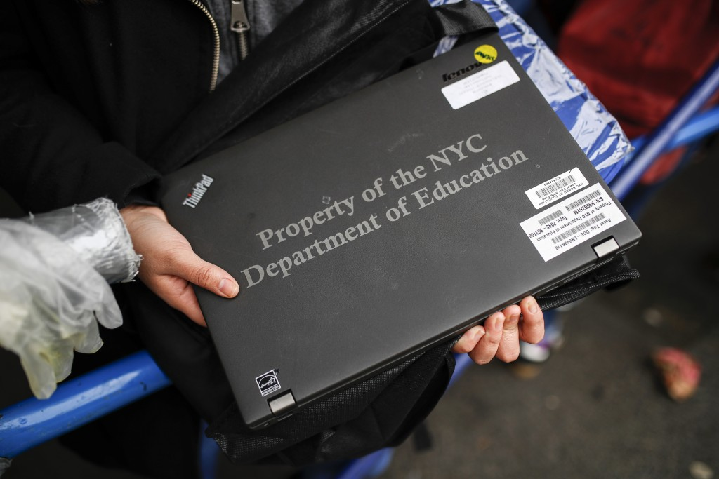 Anna Louisa, 18, receives her school laptop for home study at the Lower East Side Preparatory School Thursday, March 19, 2020, in New York, as coronav...