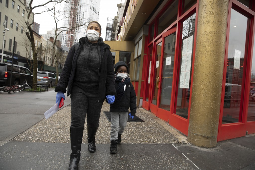 An employee of Junior's Restaurant leaves with her paycheck and her son, Thursday, March 19, 2020 in the Brooklyn borough of New York. The restaurant ...