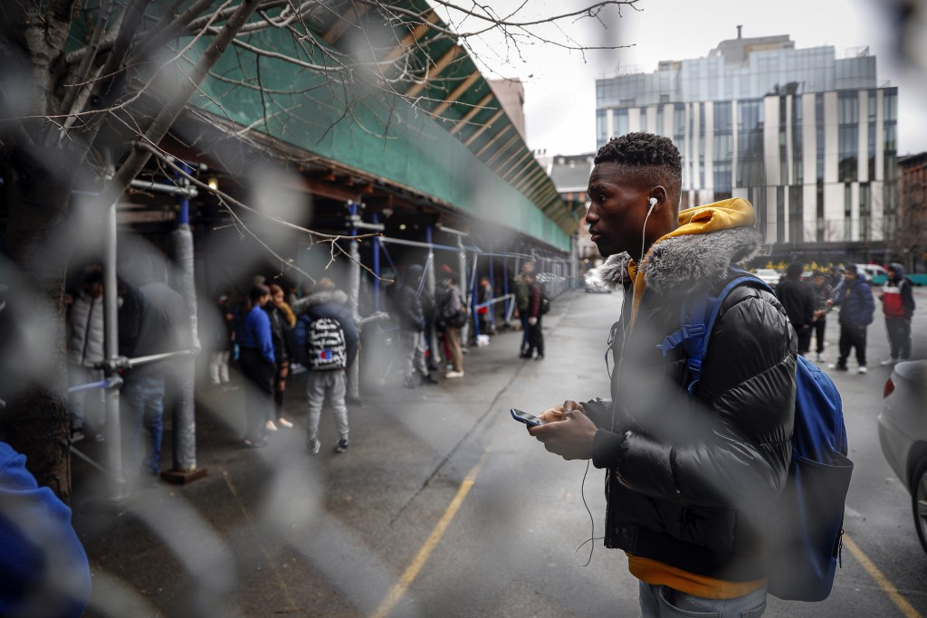 Student Laye Diakite lingers on premises after waiting to receive a school laptop for home study at the Lower East Side Preparatory School, Thursday, ...