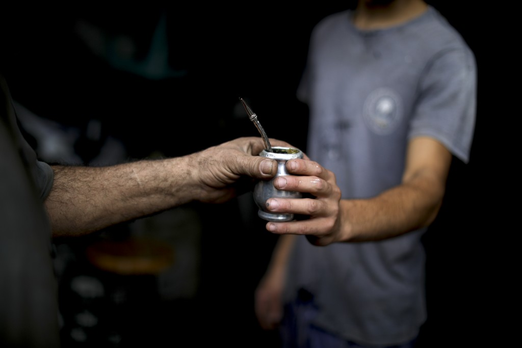 "In this March 17, 2020 photo, Oscar Brun, left, shares his ""mate"" drink with a work colleague Tomas Bravo at his ironworks shop in Buenos Aires, Argen..."