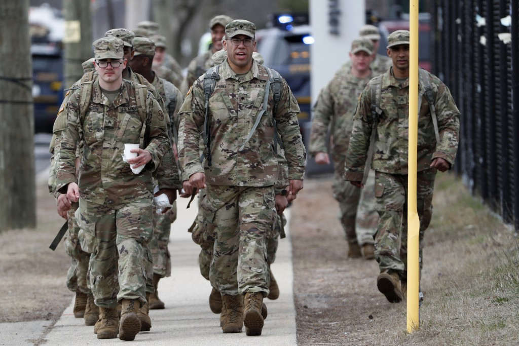 National Guard personnel march in formation as they leave duty after working Thursday, March 19, 2020, at a state-managed coronavirus drive-thru testi...