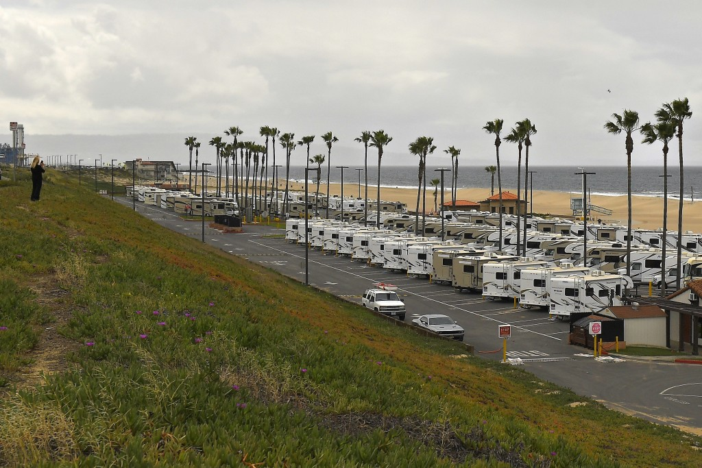 Recreational vehicles sit in a lot along Dockweiler State Beach on Thursday, March 19, 2020, in Los Angeles. Health officials are looking for quaranti...