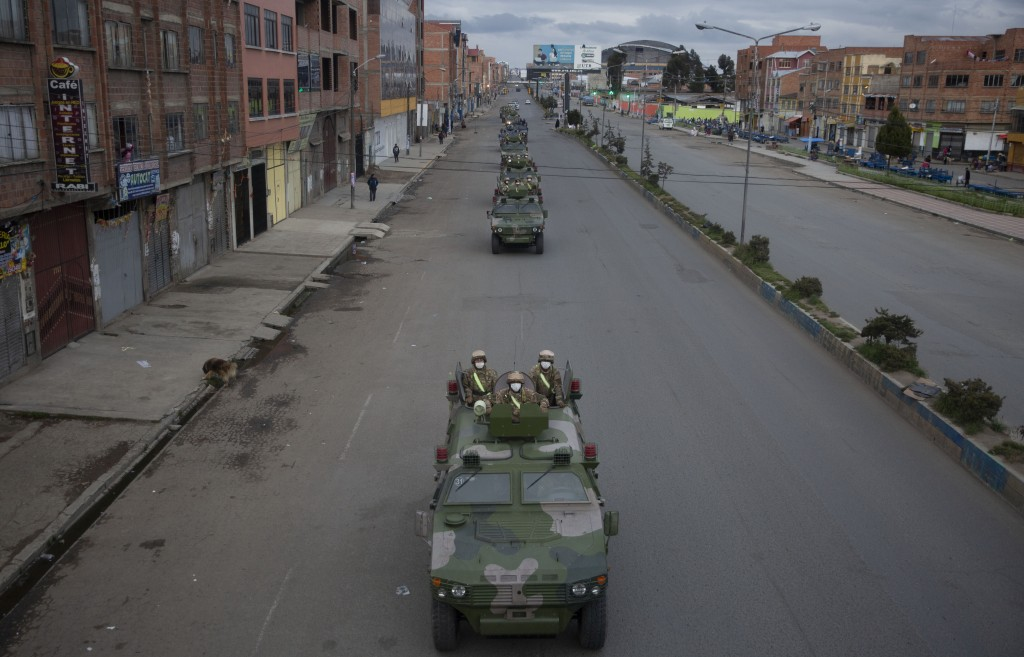 Military armored vehicles patrol the streets during a quarantine in El Alto, Bolivia, Friday, March 20, 2020. Authorities have decreed a quarantine fr...
