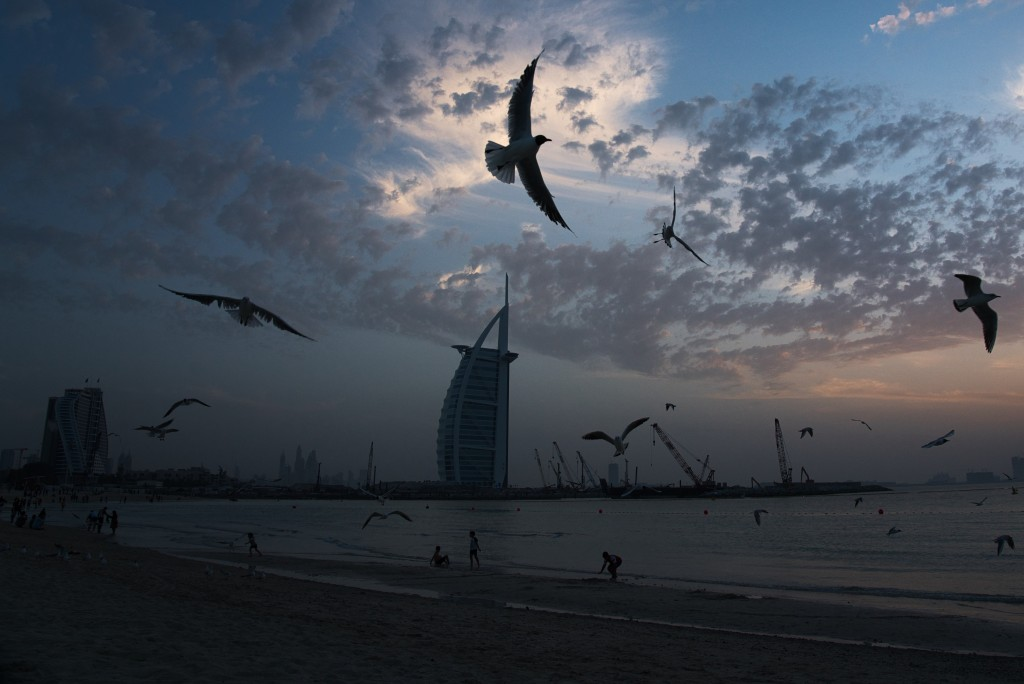 Seagulls soar over those gathered on a beach in front of the luxury Burj Al Arab hotel despite the global new coronavirus pandemic in Dubai, United Ar...