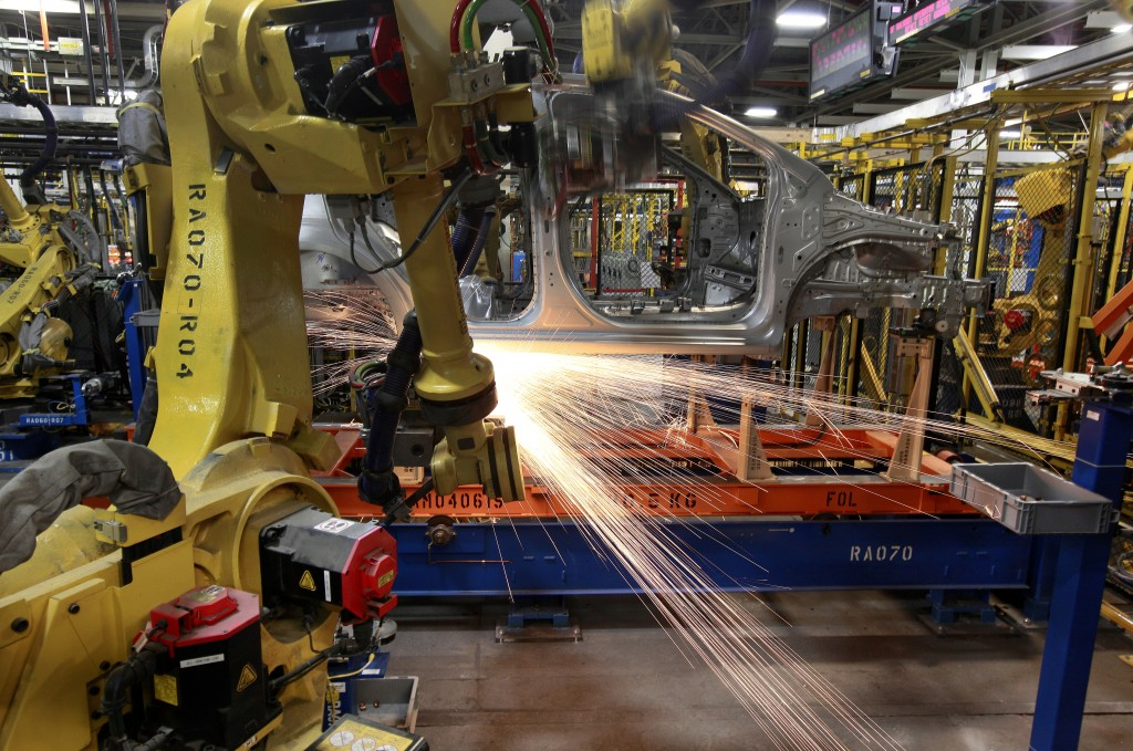 In this May 19, 2011 photo, robots weld a Chevrolet Sonic at the General Motors Orion Assembly plant in Orion Township, Mich. General Motors, Ford, je...