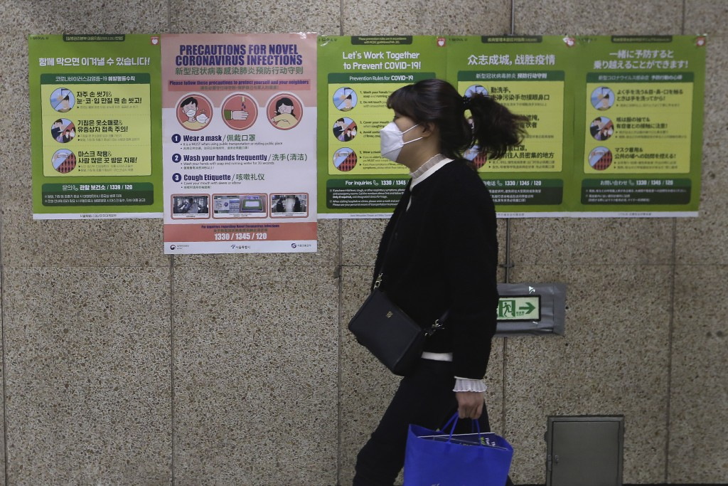 A woman wearing a face mask passes by posters about precautions against new coronavirus at a subway station in Seoul, South Korea, Saturday, March 21,...