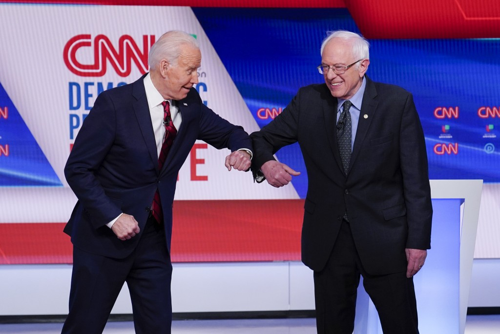 Former Vice President Joe Biden, left, and Sen. Bernie Sanders, I-Vt., right, greet one another before they participate in a Democratic presidential p...