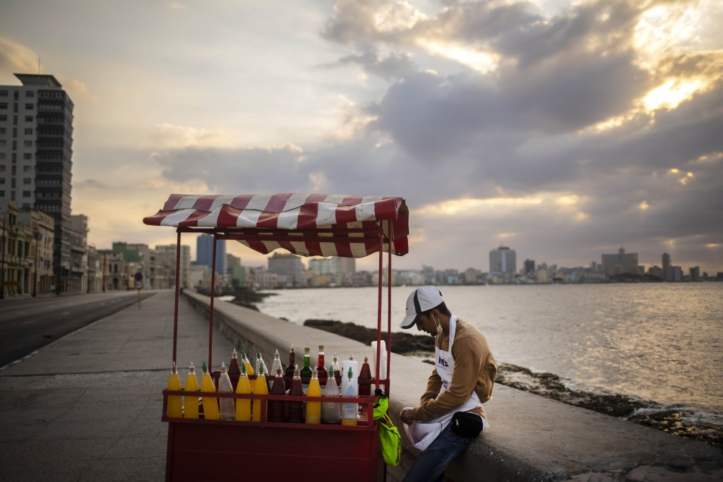 A slushy street vendor, who uses a protective face mask when he has customers as a precaution against the spread of the new coronavirus, waits for the...