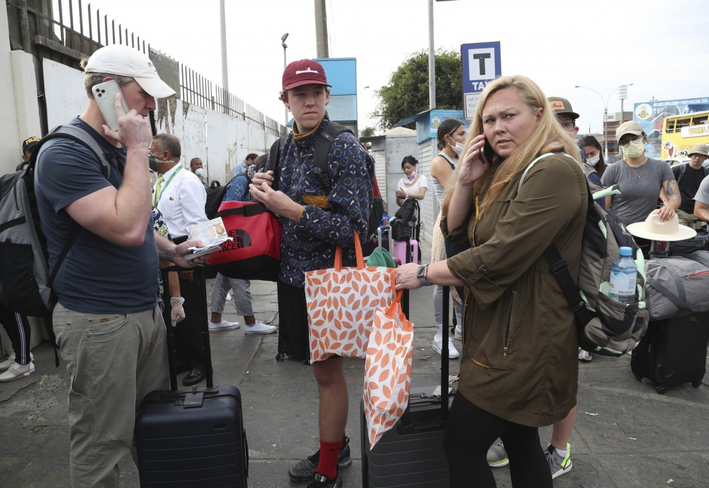Tourists from the United States wait outside the closed Jorge Chavez International Airport for a member of the U.S. Embassy to escort them to a flight...