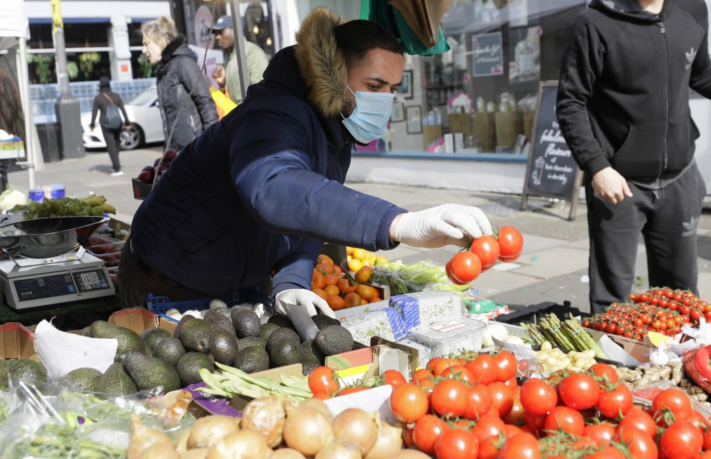 A fruit and vegetable stall holder wears a mask and gloves amid the COVID-19 virus outbreak in Portobello Road market in London, Saturday, March 21, 2...