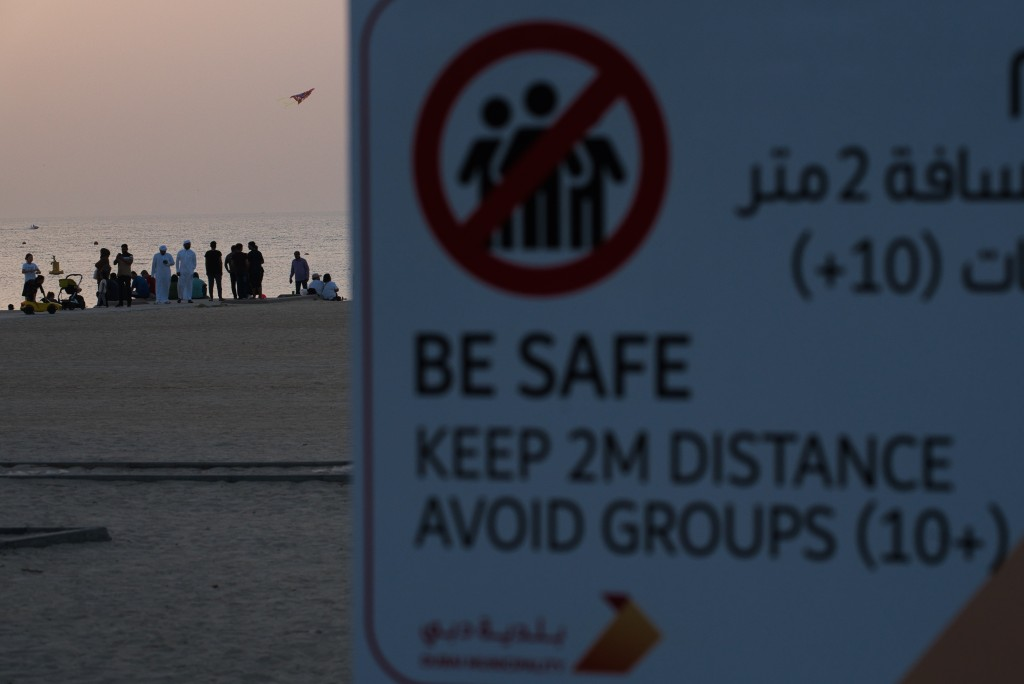 A crowd of more than 10 people gather on a beach despite a sign warning passers-by to maintain a distance from each other over the outbreak of the new...