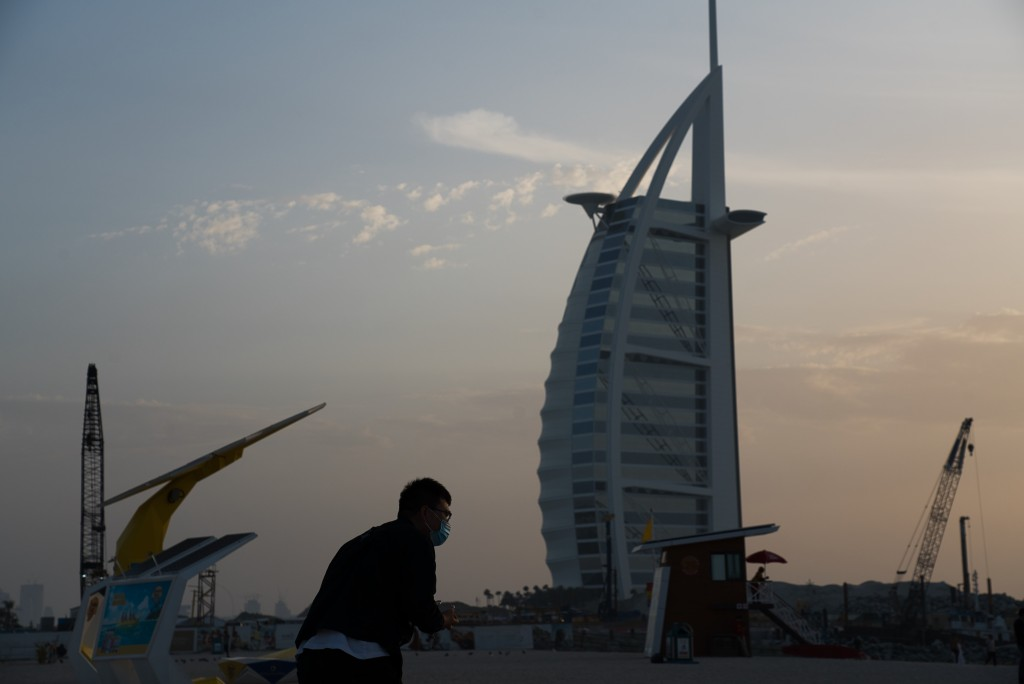 A tourist wearing a surgical mask bends down to take a picture in front of the sail-shaped Burj Al Arab luxury hotel in Dubai, United Arab Emirates, F...