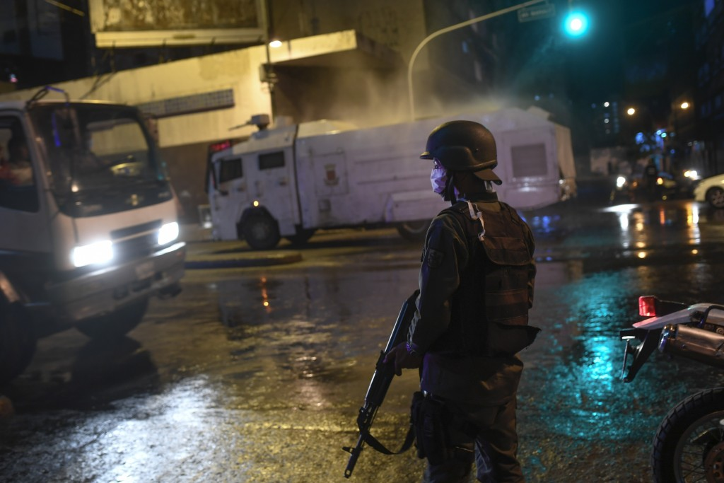 Bolivarian National Guards use a water cannon to spray disinfectant as a preventive measure against the spread of the new coronavirus, in Caracas, Ven...