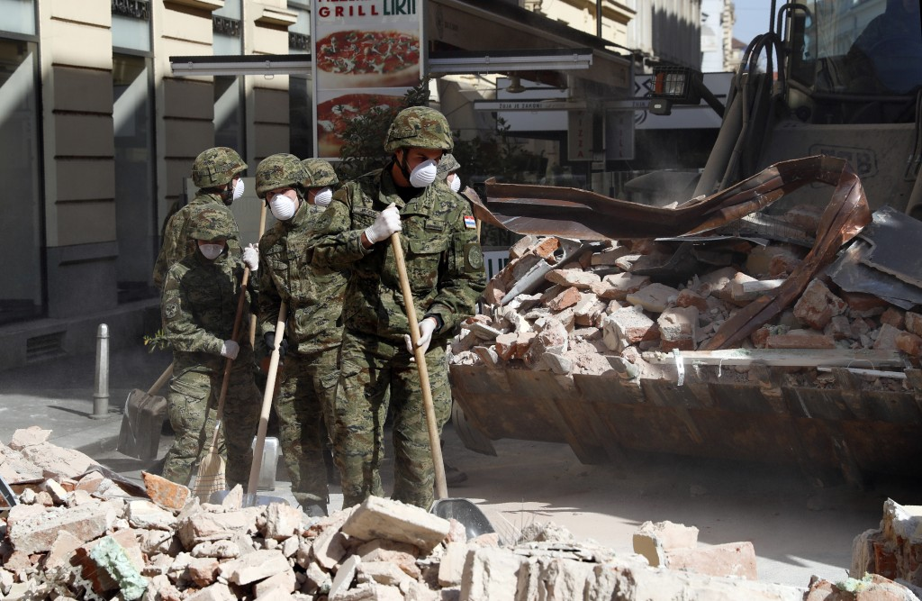 Croatian soldiers clear debris from the street after an earthquake in Zagreb, Croatia, Sunday, March 22, 2020. A strong earthquake shook Croatia and i...