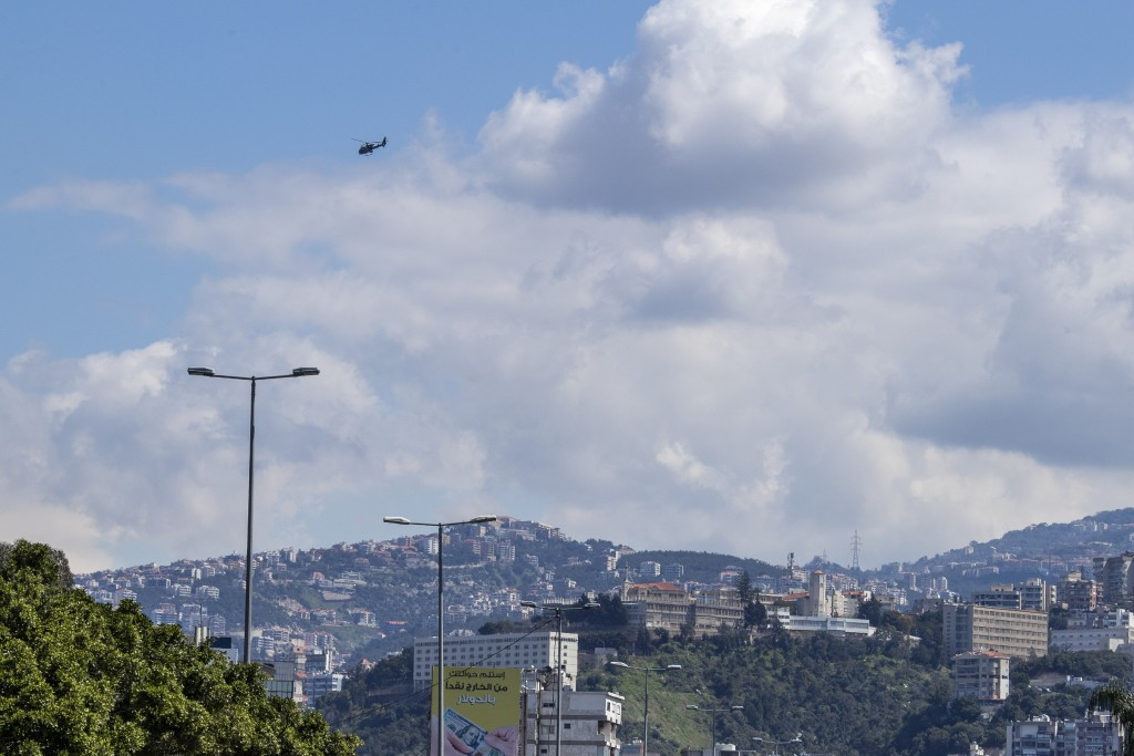 A Lebanese army helicopter flies over east Beirut, after flying lower over neighborhoods using loudspeakers to urge people to stay home unless they ha...