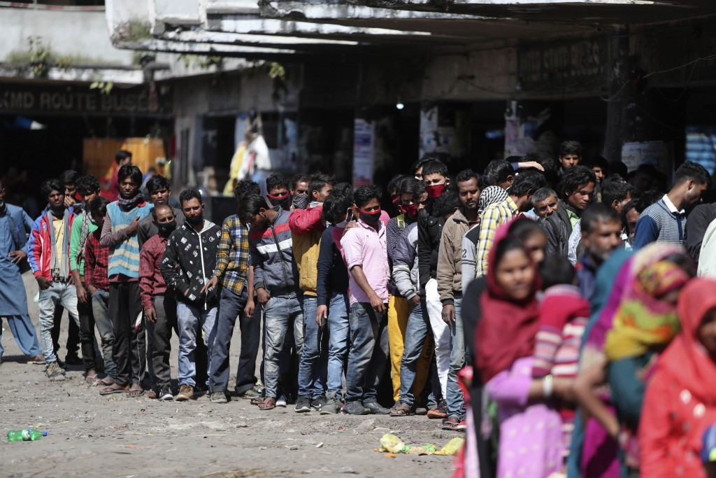 Indian passengers who got stranded at a bus terminal line up for free food being distributed by shop keepers during a day long lockdown amid growing c...