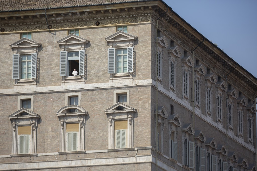 Pope Francis delivers his blessing from the window of his private library overlooking an empty St. Peter's Square, at the Vatican, Sunday, March 22, 2...