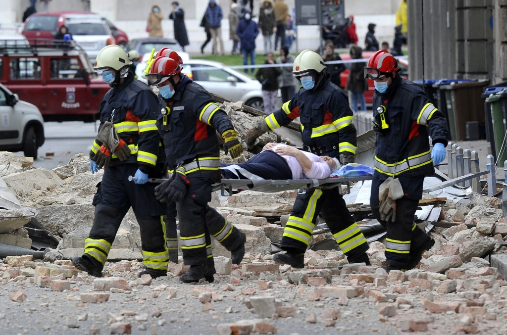 Firefighters carry a person on a stretcher after an earthquake in Zagreb, Croatia, Sunday, March 22, 2020. A strong earthquake shook Croatia and its c...