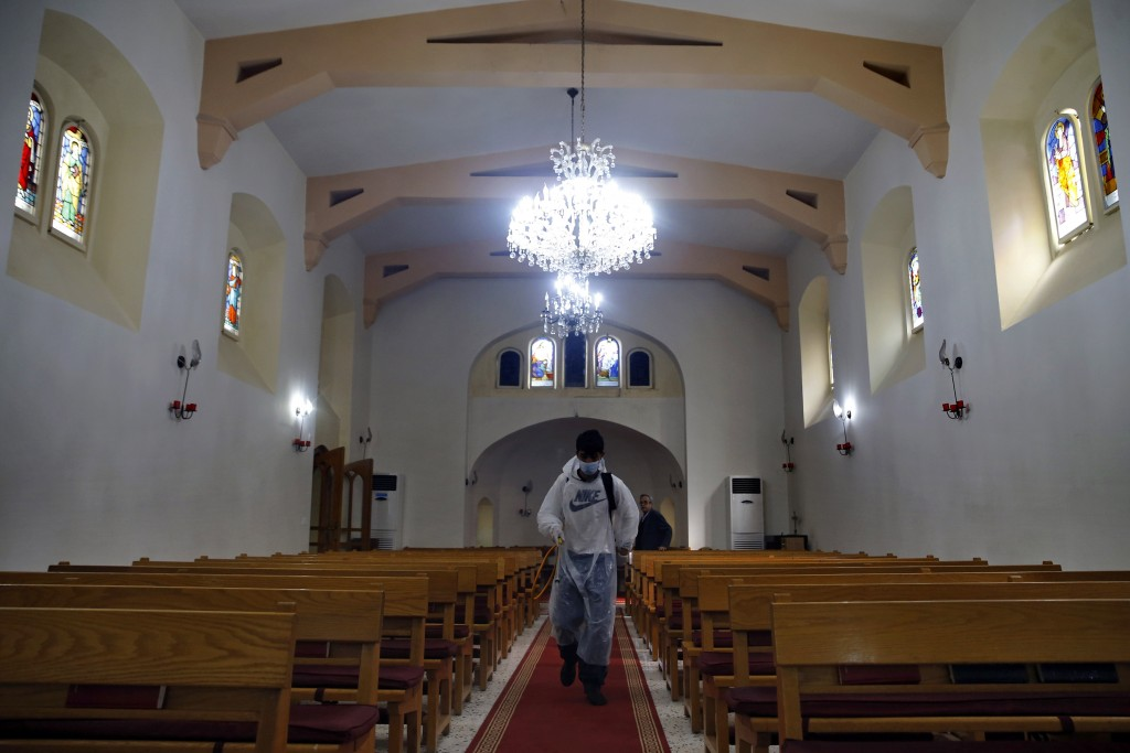 A municipal worker wearing protective gear sprays spray disinfectant as a precaution against the coronavirus, at a church in Beirut, Lebanon, Sunday, ...