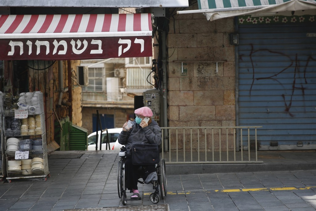 A woman sits in a mostly closed market in Jerusalem, Sunday, March 22, 2020. Police officers ordered owners to shut down their shops at the food marke...