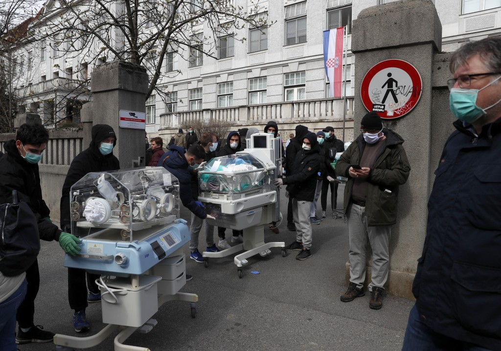 People carry incubators for newborn babies as the hospital is evacuated after an earthquake in Zagreb, Croatia, Sunday, March 22, 2020. A strong earth...