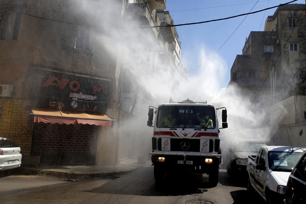 A municipal tanker sprays disinfectant as a precaution against the coronavirus outbreak in Beirut, Lebanon, Sunday, March 22, 2020. Lebanon has been t...