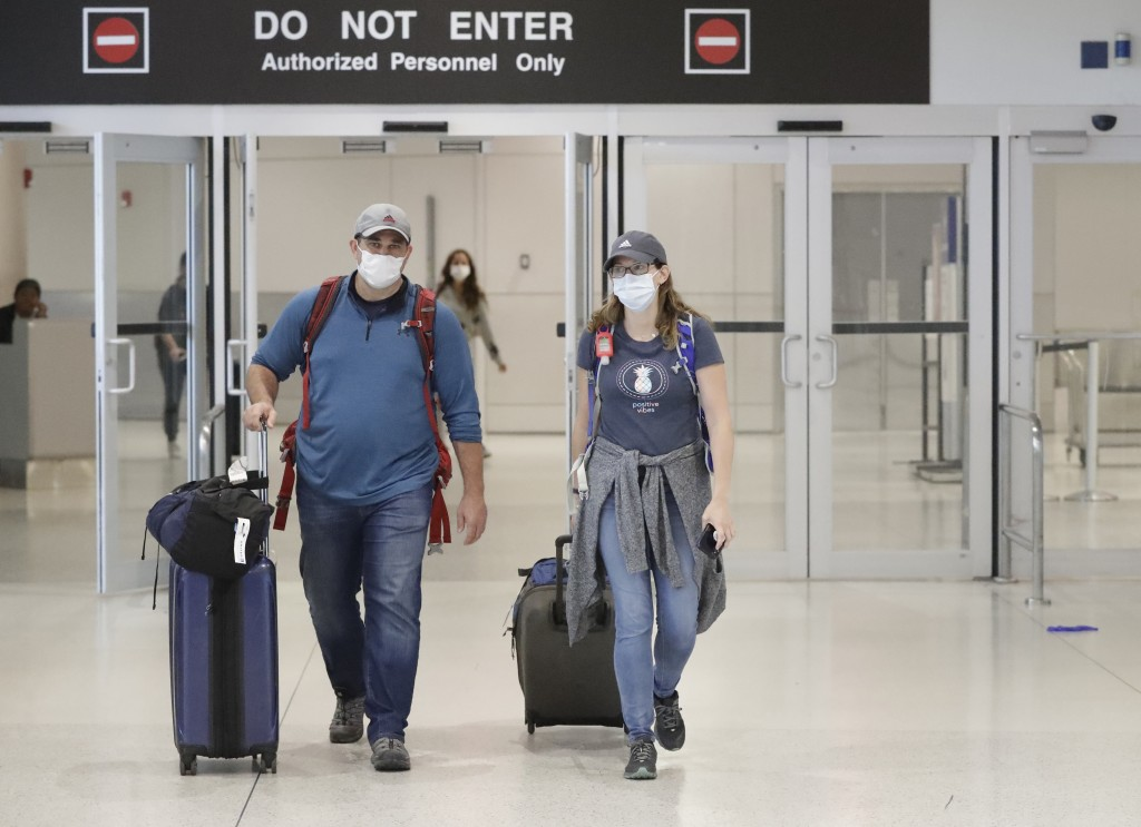 Mike Rustici, left, and Linda Scruggs exit customs after arriving on a flight from Lima, Peru, Saturday, March 21, 2020, at Miami International Airpor...
