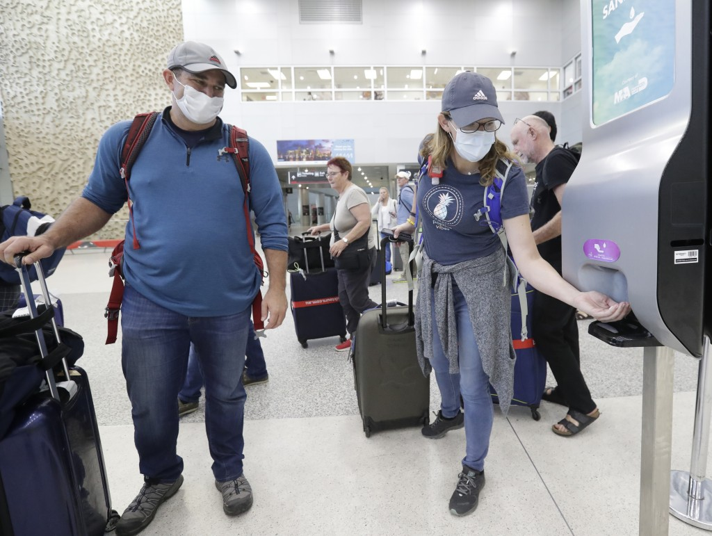 Linda Scruggs, right, applies hand sanitizer as Mike Rustici, left, watches after they arrived on a flight from Lima, Peru, Saturday, March 21, 2020, ...