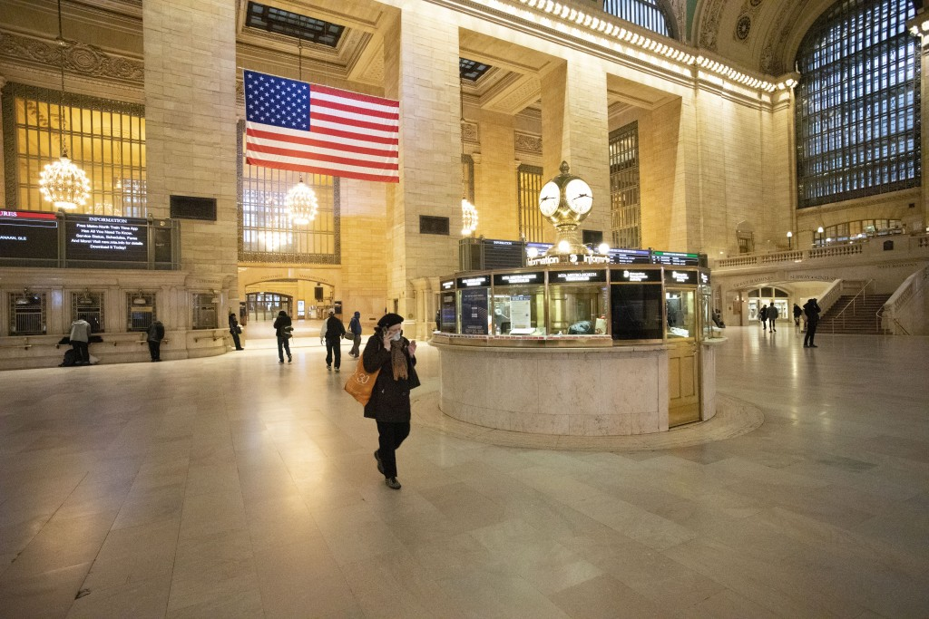 Commuters pass through Grand Central Terminal during the morning rush hour, Monday, March 23, 2020, in New York. Gov. Andrew Cuomo has ordered most Ne...