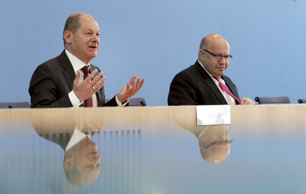 German Finance Minister Olaf Scholz, left, and German Economy Minister, Peter Altmaier, right, address the media in Berlin, Germany, Monday, March 23,...
