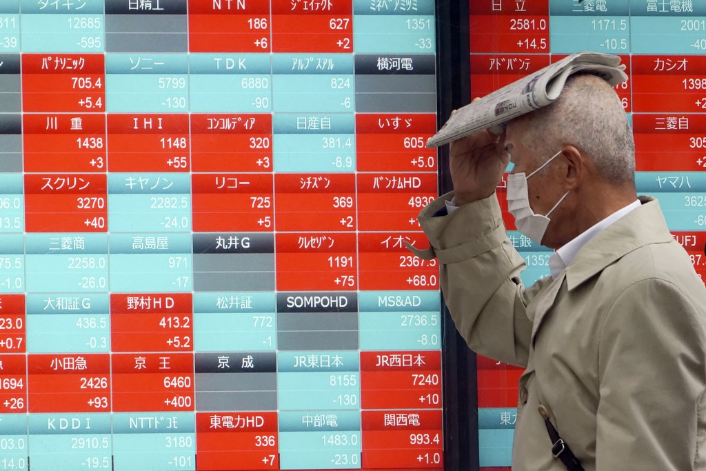 A man with a protective mask in the rain looks at an electronic stock board showing Japan's Nikkei 225 index at a securities firm in Tokyo Monday, Mar...