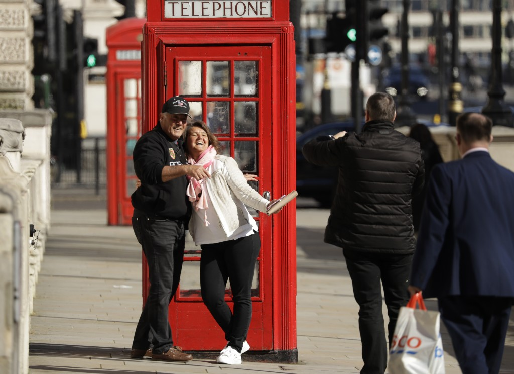 Two tourist have their photo taken next to a traditional red telephone box in Westminster, London, Monday, March 23, 2020. The British government is e...