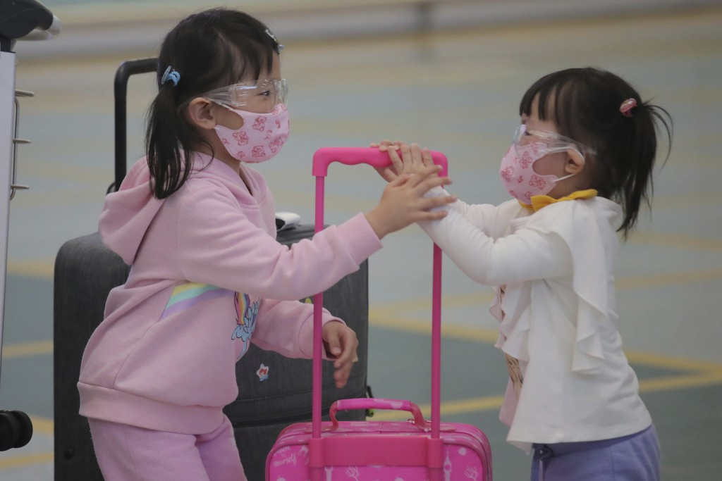 Young passengers wear face masks to protect against the coronavirus as they arrive at the Hong Kong airport, Monday, March 23, 2020. For most, the cor...