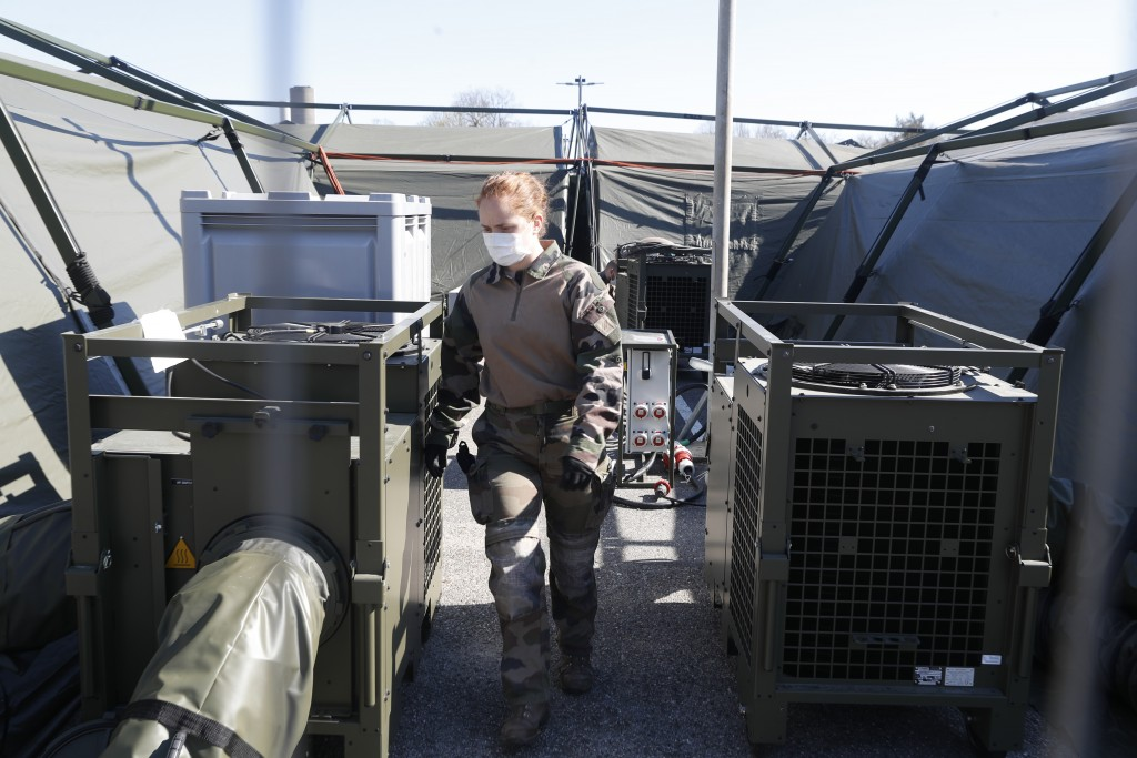 A soldier walks by equipments ar the Mulhouse military makeshift hospital build in Mulhouse, eastern France, Monday March 23, 2020. The Grand Est regi...