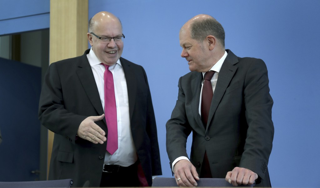 German Economy Minister, Peter Altmaier, left, tries to shake hands with German Finance Minister Olaf Scholz, right, prior to a press conference in Be...