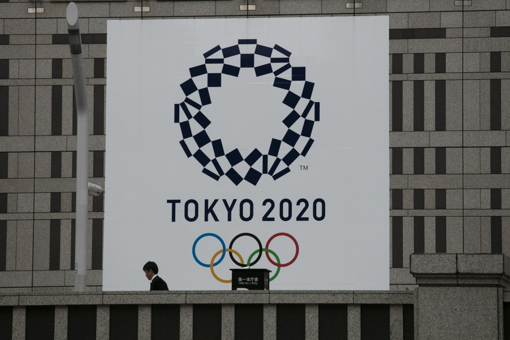 A man walks past a large banner promoting the Tokyo 2020 Olympics in Tokyo, Monday, March 23, 2020. The International Olympic Committee on Tuesday pos...