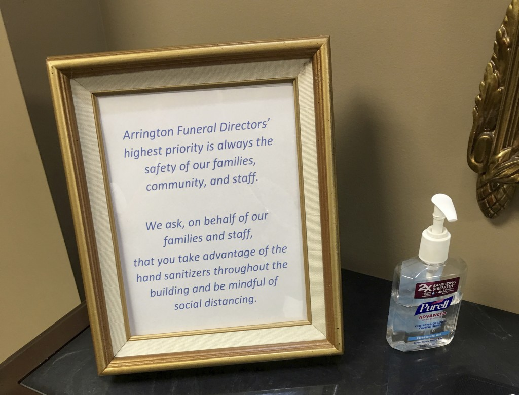 This March 19, 2020, photo provided by Bob Arrington of Arrington Funeral Directors shows a sign requesting visitors to use hand sanitizer and maintai...