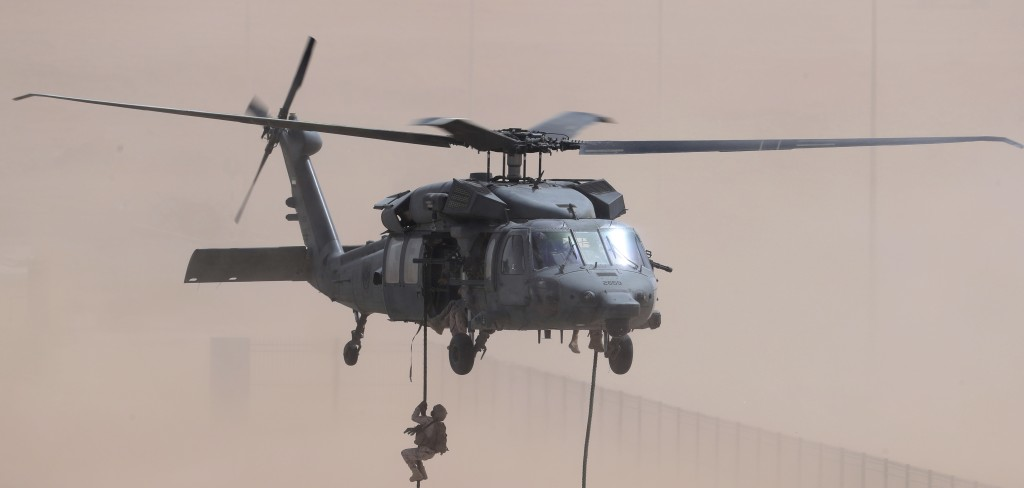 An Emirati soldier rappels out of a Sikorsky UH-60 Black Hawk during an exercise at an Emirati military base home to a Military Operations in Urban Te...