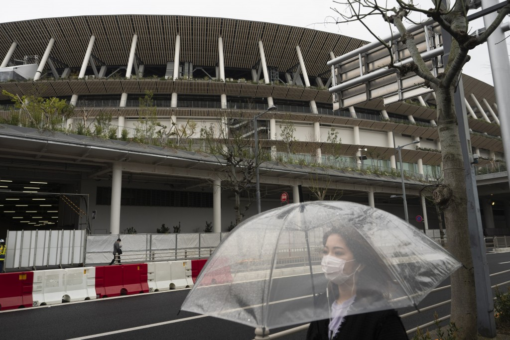 A woman walks past the New National Stadium, a venue for the opening and closing ceremonies at the Tokyo 2020 Olympics, in Tokyo, Monday, March 23, 20...