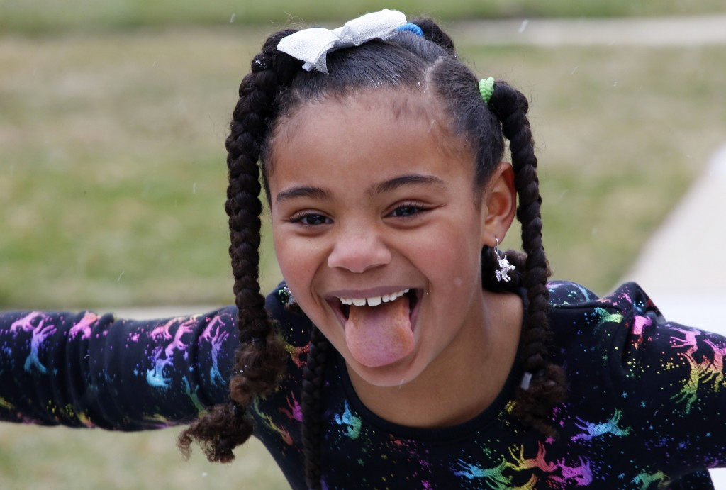 Sydney Grimes, 7, sticks her tongue out to catch a snowflake outside their Chicago neighborhood on Sunday, March 22, 2020. Her mom says she's less awa...