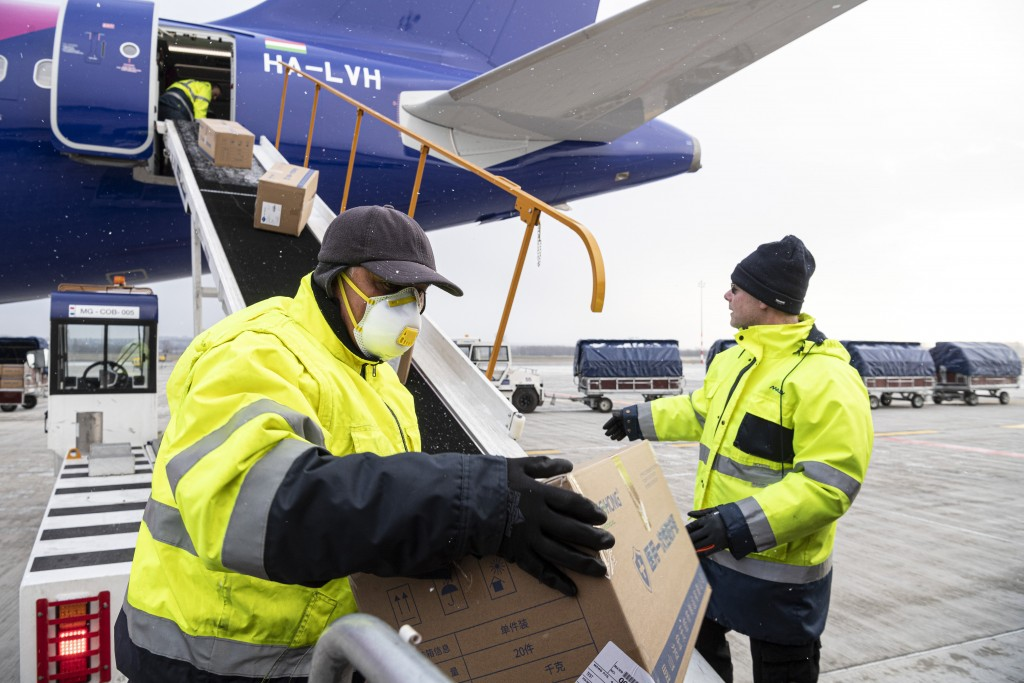 Workers unload boxes containing medical aid and protective materials to combat the COVID-19 coronavirus from a plane of the Hungarian low-cost airline...
