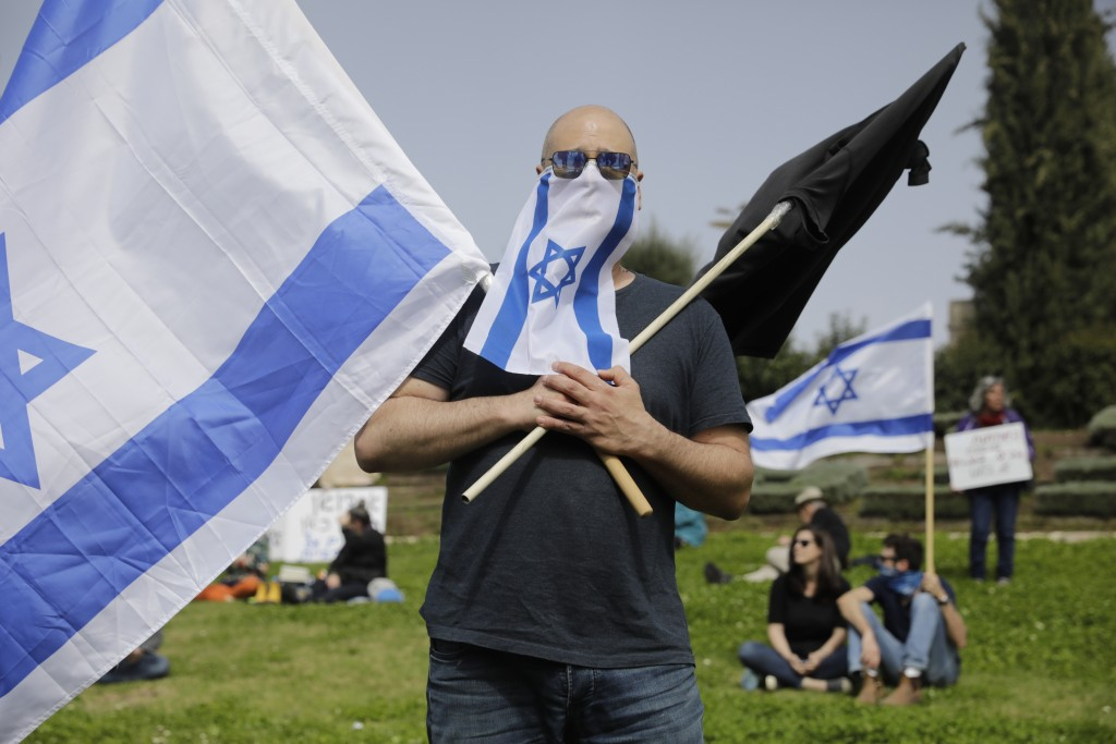 Israelis hold national flags during a protest against Prime Minister Benjamin Netanyahu outside the national parliament in Jerusalem, Monday, March 23...