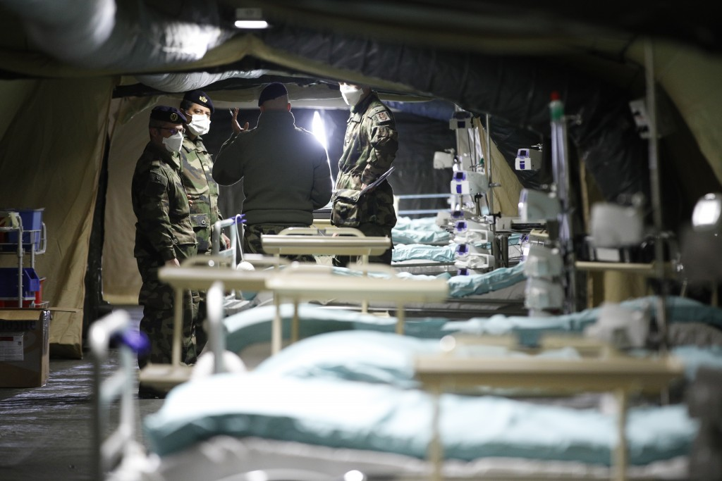 French soldiers discuss inside the military field hospital built in Mulhouse, eastern France, Monday March 23, 2020. The Grand Est region is now the e...